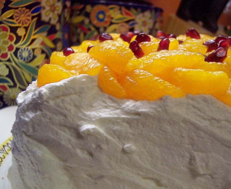 Vanilla Cake with oranges and pomegranates on cream